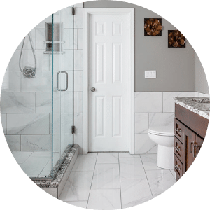 Natural Stone Glass Framed Shower and Stone Flooring with Stone Half Walls in Beautiful Modern Des Moines Bathroom Remodel | Compelling Homes