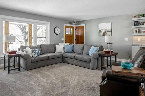 Whole Home Remodel Living Room with Floating Shelves Large Windows and Comfortable Sectional Couch | Compelling Homes