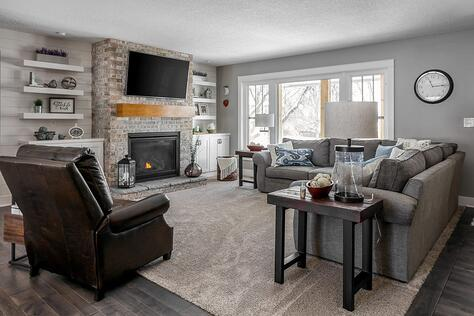 Whole Home Remodel Living Room with Stone Fireplace Floating Shelves Oversized Windows and Custom TV Built-Ins | Compelling Homes