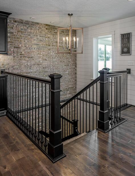 Whole Home Remodel with Stone Accent Wall Leading Downstairs with Modern Stair Railing and Shiplap Wall | Compelling Homes