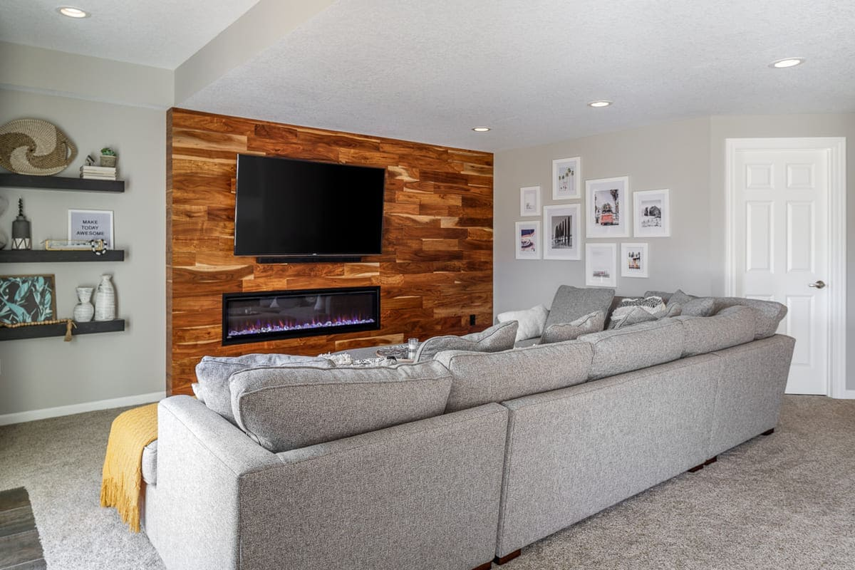 Basement Remodel Hardwood Flooring Accent Wall with Built-In Electric Fireplace Lots of Natural Light and Gallery Wall | Compelling Homes Remodeling & Design
