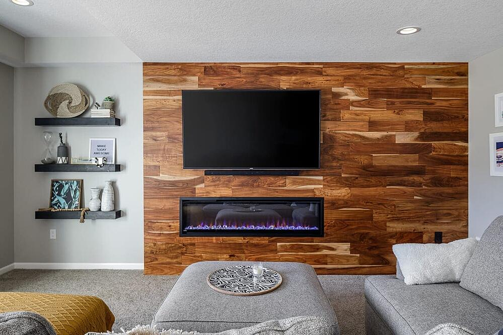 Basement Remodel Hardwood Flooring Accent Wall with Electric Built-In Fireplace and Floating Shelves Lots of Natural Light | Compelling Homes Remodeling & Design