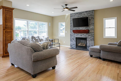 Full-Home Remodel Living Room with Stone Accent Wall Mantlepiece and Fireplace Open Floor Concept