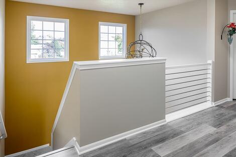Full-Home Remodel Yellow Accent Wall with Industrial Accent Lighting and Conduit Railing
