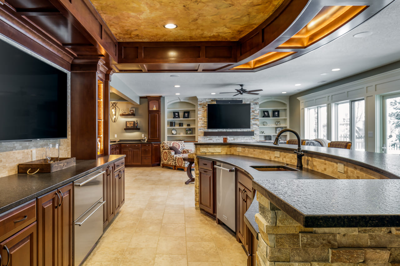 Custom Bar Overlooking Living Room and Custom Buffet Area for Entertaining in Large Walk Out Basement Remodel with Natural Light | Compelling Homes Des Moines, IA
