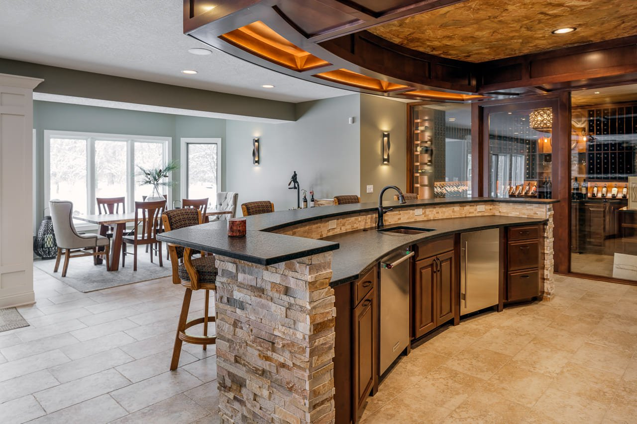 Custom Bar with Wine Cellar and Kitchen Area Overlooking Dining Room with Natural Light in Walk Out Basement | Compelling Homes Des Moines, IA