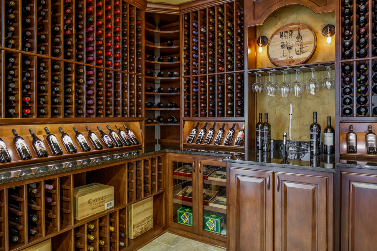 In-Home Wine Cellar with Custom Shelving Units and Tasting Area in Walk Out Basement | Compelling Homes Des Moines, IA