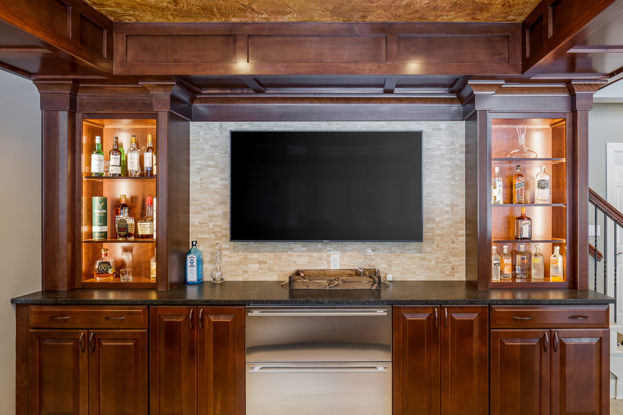 Stone Accent TV Wall Behind Custom Bar in Walk Out Basement with Lots of Natural Light | Compelling Homes Des Moines, IA