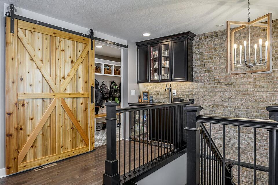 Whole Home Remodel Sliding Barn Door into Mudroom with Walk-Up Bar and Stone Accent Wall _ Compelling Homes