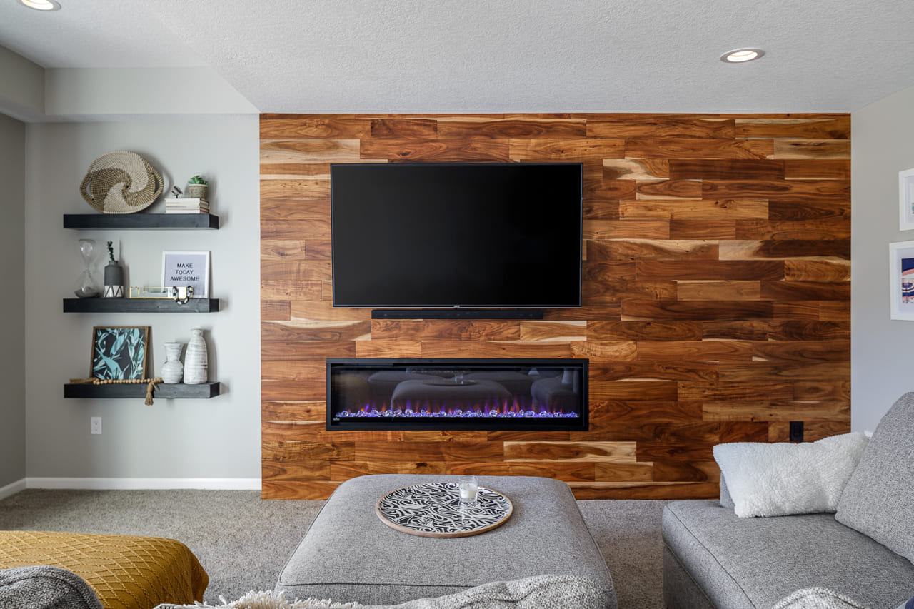 Basement Remodel Hardwood Flooring Accent Wall with Electric Built-In Fireplace and Floating Shelves Lots of Natural Light _ Compelling Homes Remodeling & Design