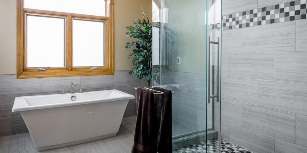 How Much Does a Bathroom Remodel Cost in Des Moines_ _ Freestanding Tub and Walk-In Glass Shower in Modern Bathroom _ Compelling Homes, Des Moines, IA